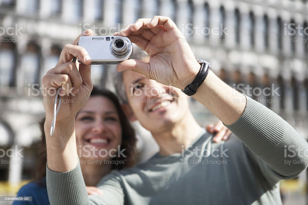 Italy, Venice, couple outdoors, man taking photograph, smiling royalty-free stock photo