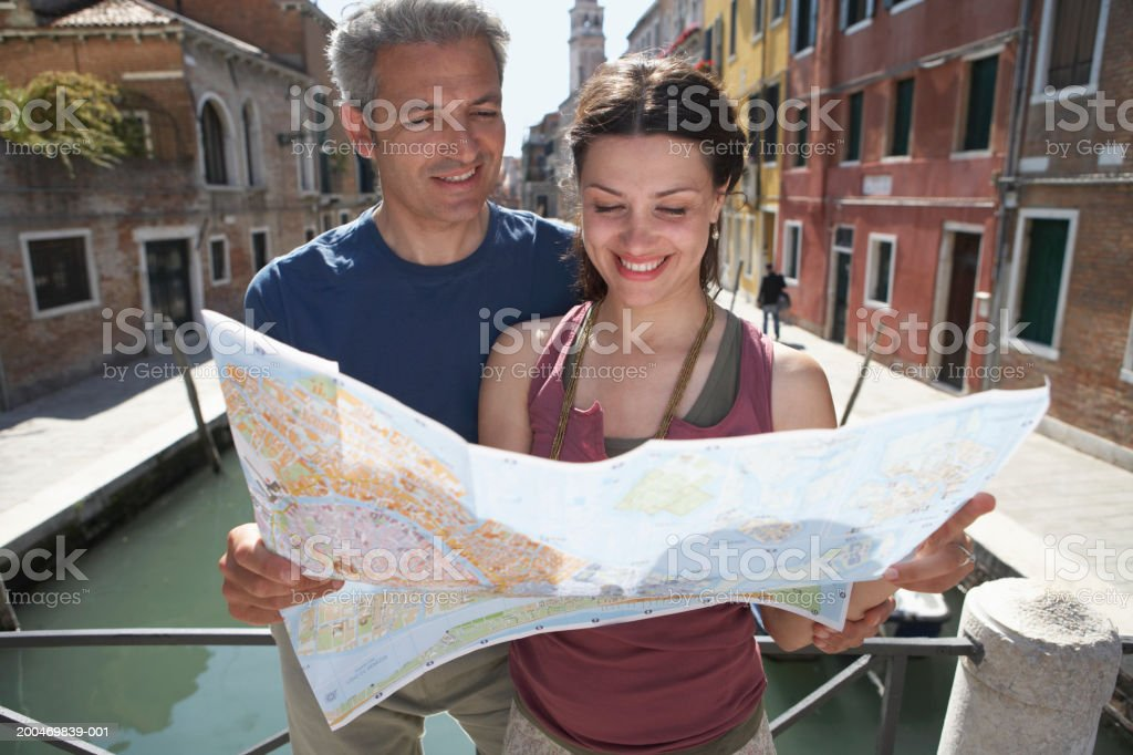 Italy, Venice, couple reading map by canal, smiling royalty-free stock photo