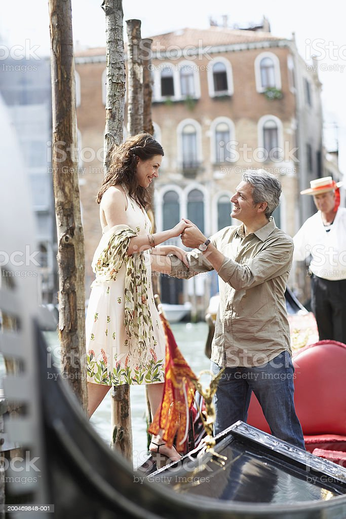Italy, Venice, man helping woman board gondola, smiling stock photo