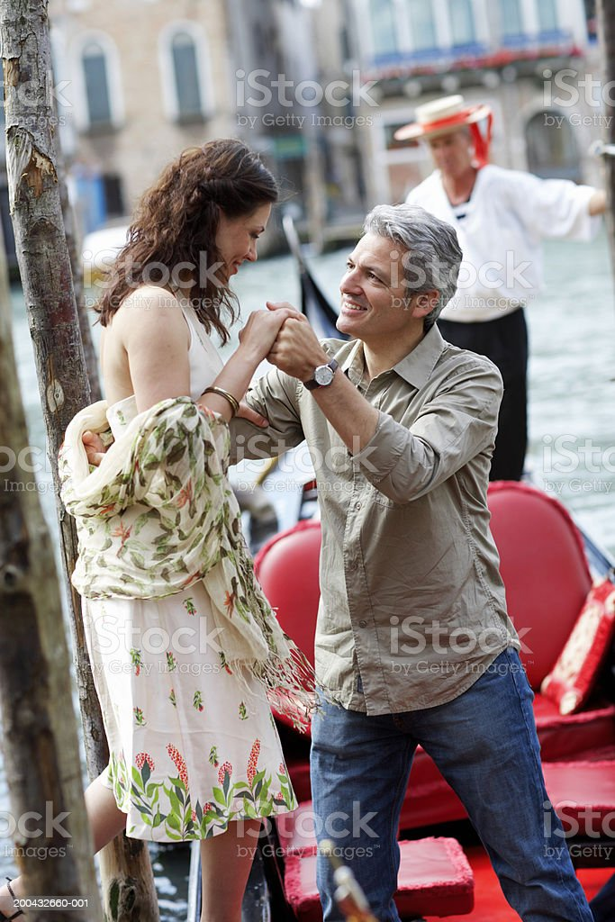 Italy, Venice, man helping woman climb into gondola royalty-free stock photo