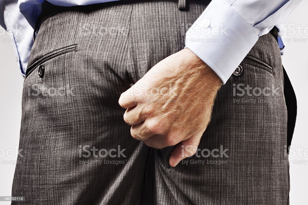 Itchy businessman rudely scratches his bottom stock photo