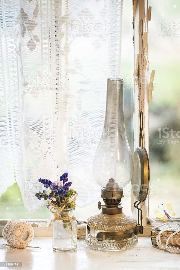 Iterior window with vintage lamp and wildflowers stock photo