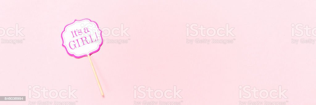 It's a girl sign at the baby shower party.  Pink solid background.  Baby shower celebration concept stock photo