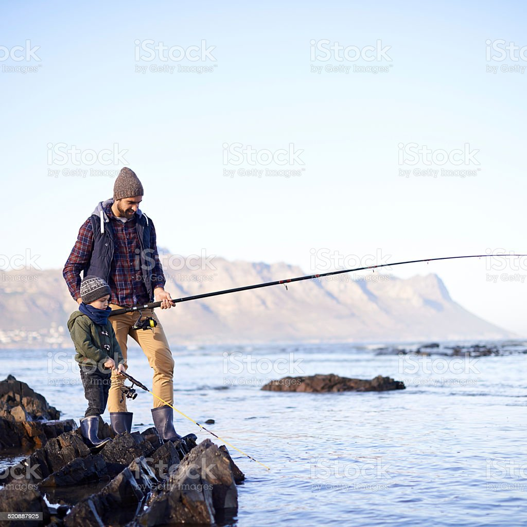 It's his first fishing trip with dad stock photo