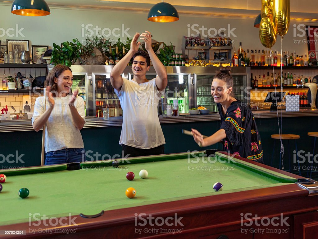 It's in: young adults cheer pub pool table success stock photo