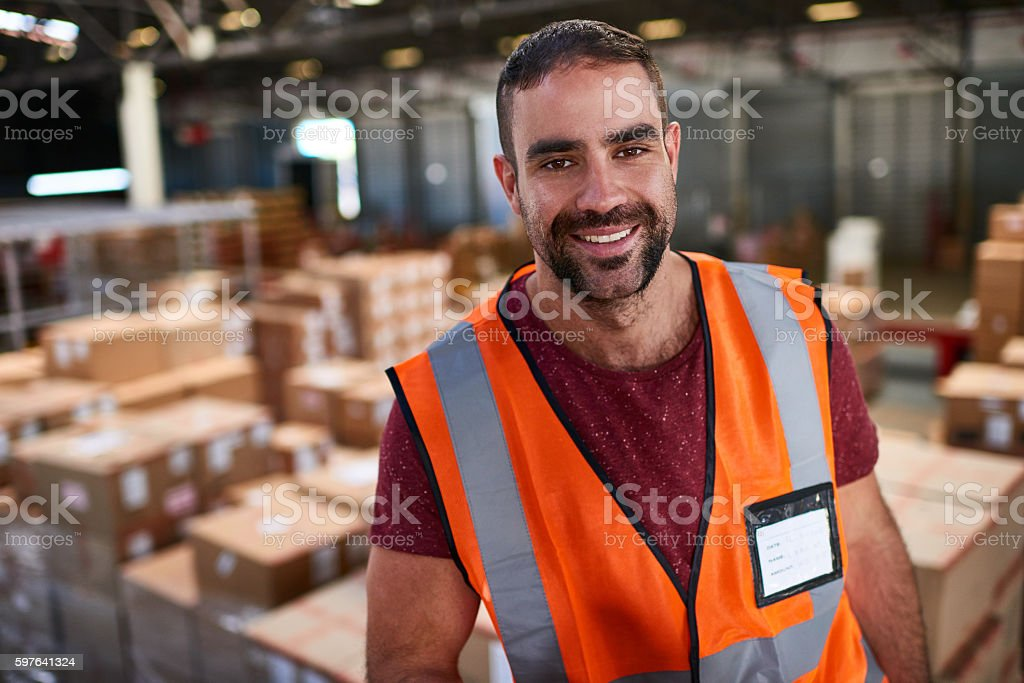 Portrait of a worker standing in a large warehouse full of boxes