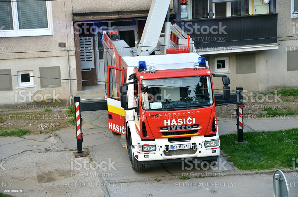 Iveco Eurocargo fire truck in action, some house in background. stock photo