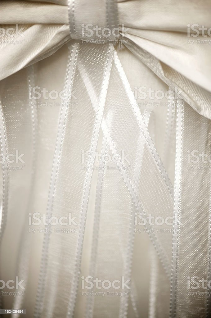 Satin ribbons hang down like a curtain from ivory silk wedding favor