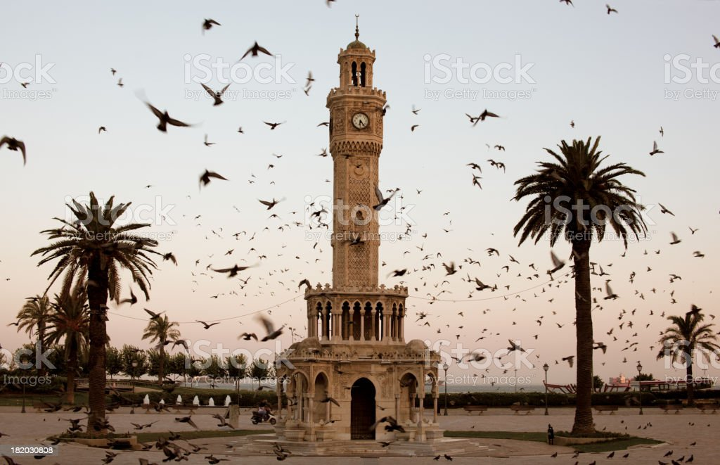 Izmir Clock Tower surrounded by flock of birds at dusk stock photo