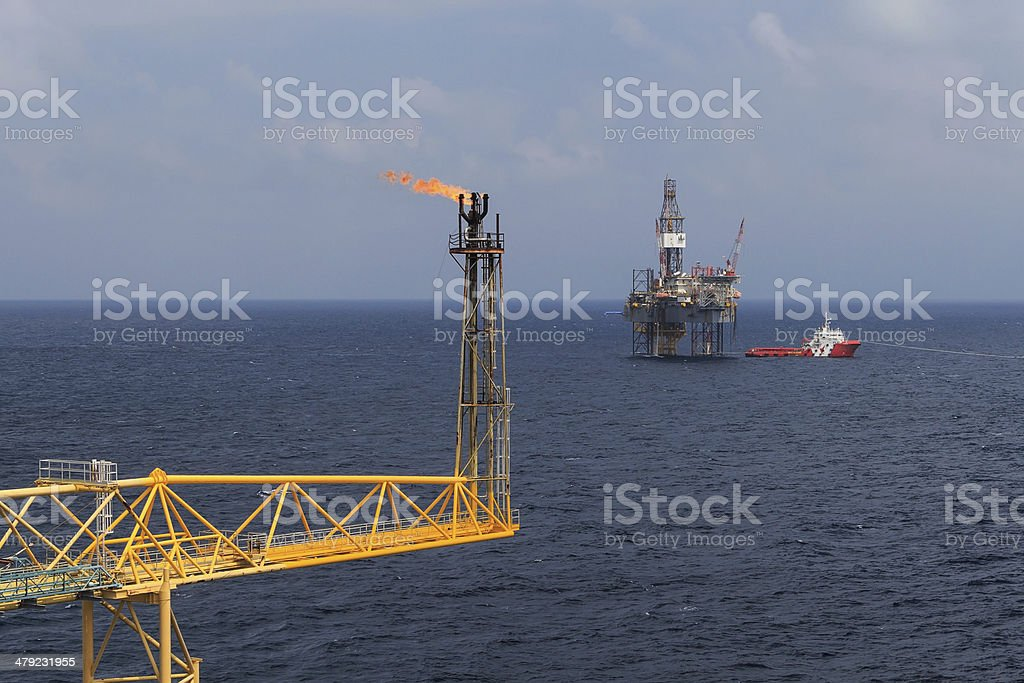 Jack up drilling rig, flare boom, and crew boat stock photo