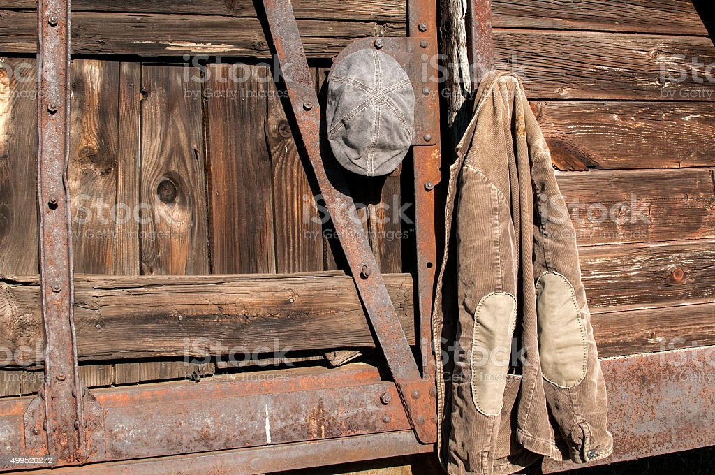 Jacket and cap on wooden wall stock photo