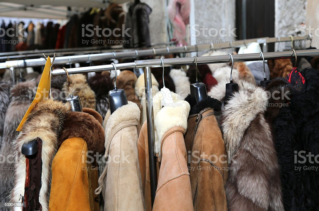 jackets fur coat hanging and second-hand clothes stock photo