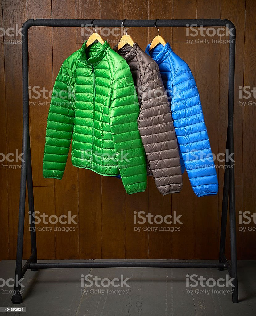 jackets hanging on a rack with a wooden background stock photo