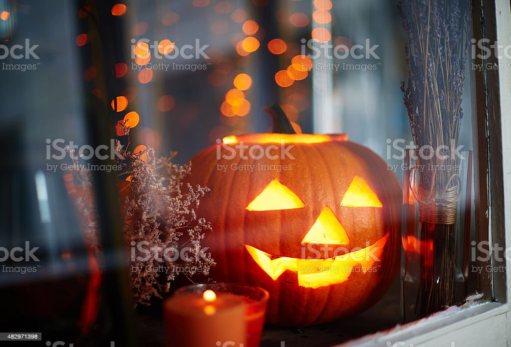 Jack-o-lantern in window stock photo
