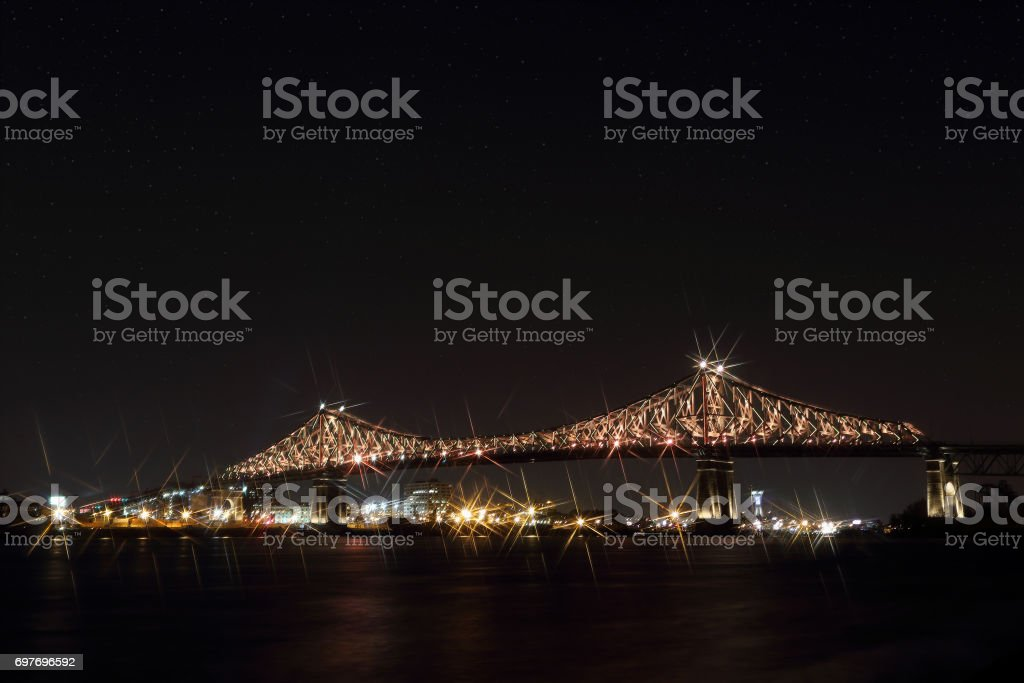 Jacques Cartier Bridge Illumination in Montreal, reflection in water. Montreal's 375th anniversary. luminous colorful interactive Jacques Cartier Bridge. Bridge panoramic colorful silhouette by night. stock photo