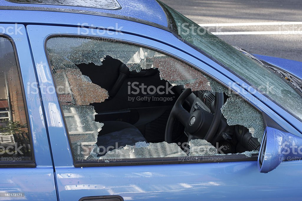 Window smashed by car thief street scene stock photo