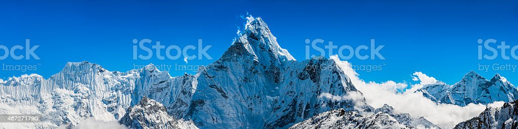 Jagged snowy mountain peaks panorama soaring above clouds Himalayas Nepal stock photo
