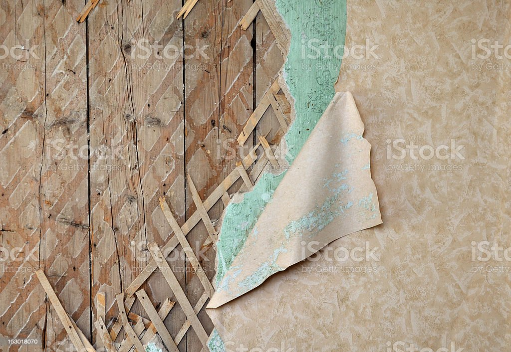 Jagged wallpaper on old destroyed wall stock photo