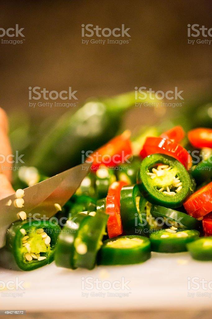 Jalapeno peppers (capsicum annuum) being sliced with knife stock photo