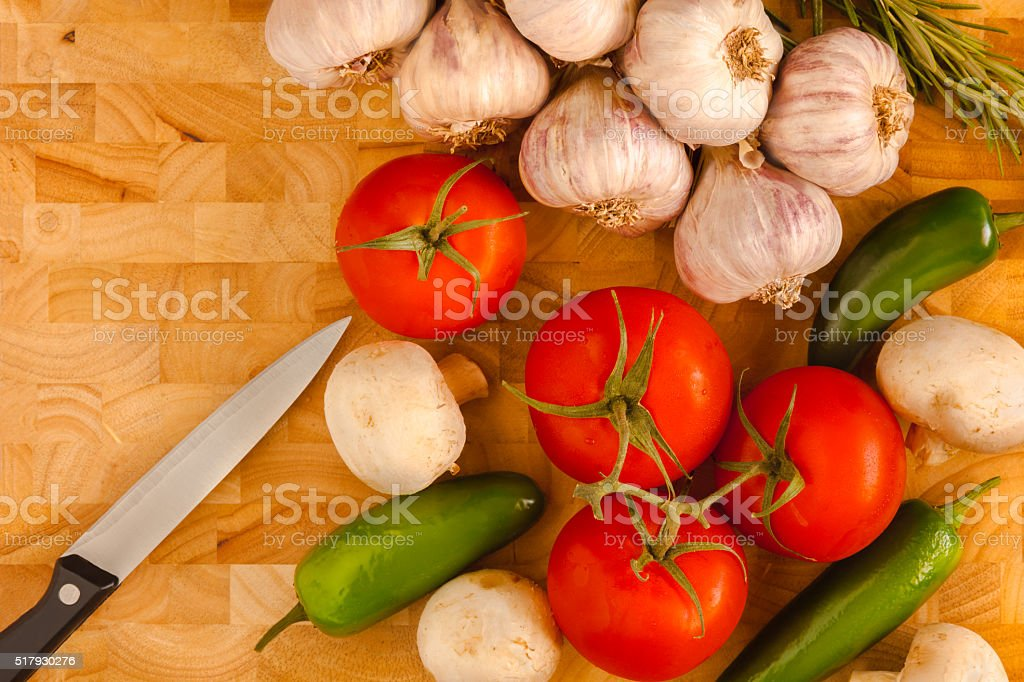 Jalapeno Peppers,Tomatoes,Mushrooms, Garlic, Knife on chopping board (P) stock photo