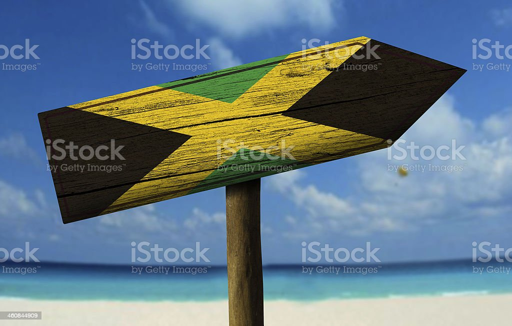 Jamaica flag wooden sign with a beach on background stock photo