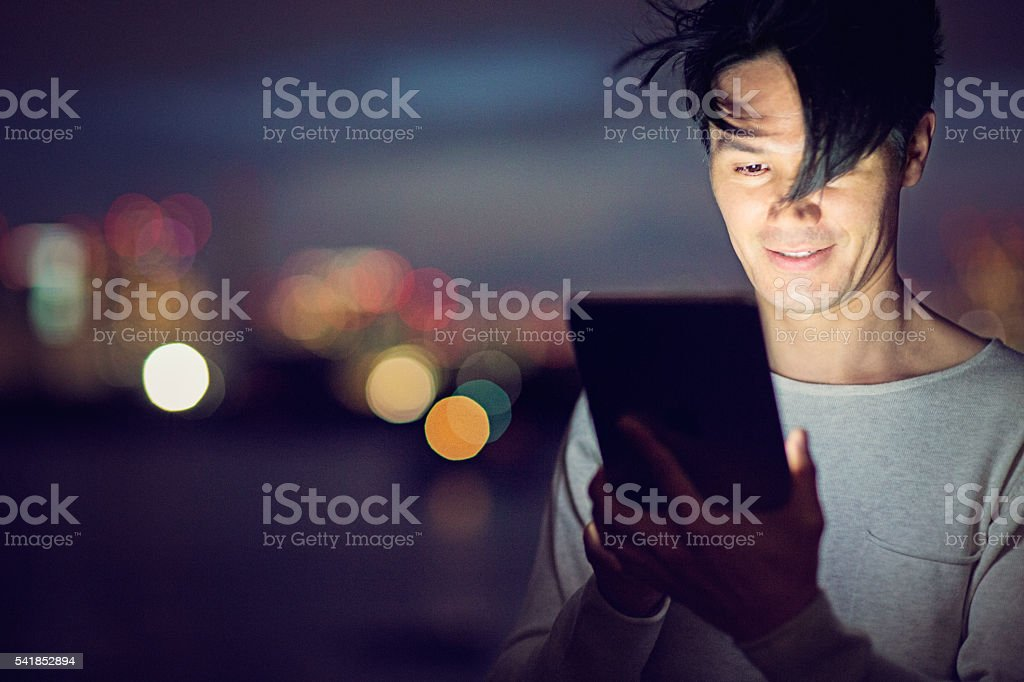 Jamanese man with tablet in the the night stock photo