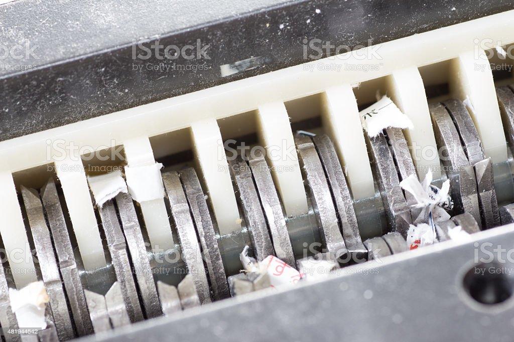 Jammed shredder scraps between paper shredder blades stock photo