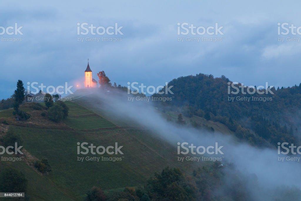 Jamnik church on a hillside in autumn, foggy weather at sunset stock photo