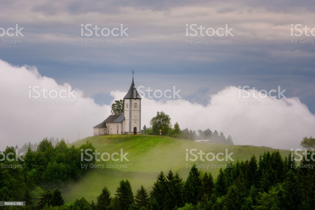 Jamnik church on a hillside in the spring, foggy weather at sunset in Slovenia, Europe. Mountain landscape shortly after spring rain. Slovenian Alps. stock photo