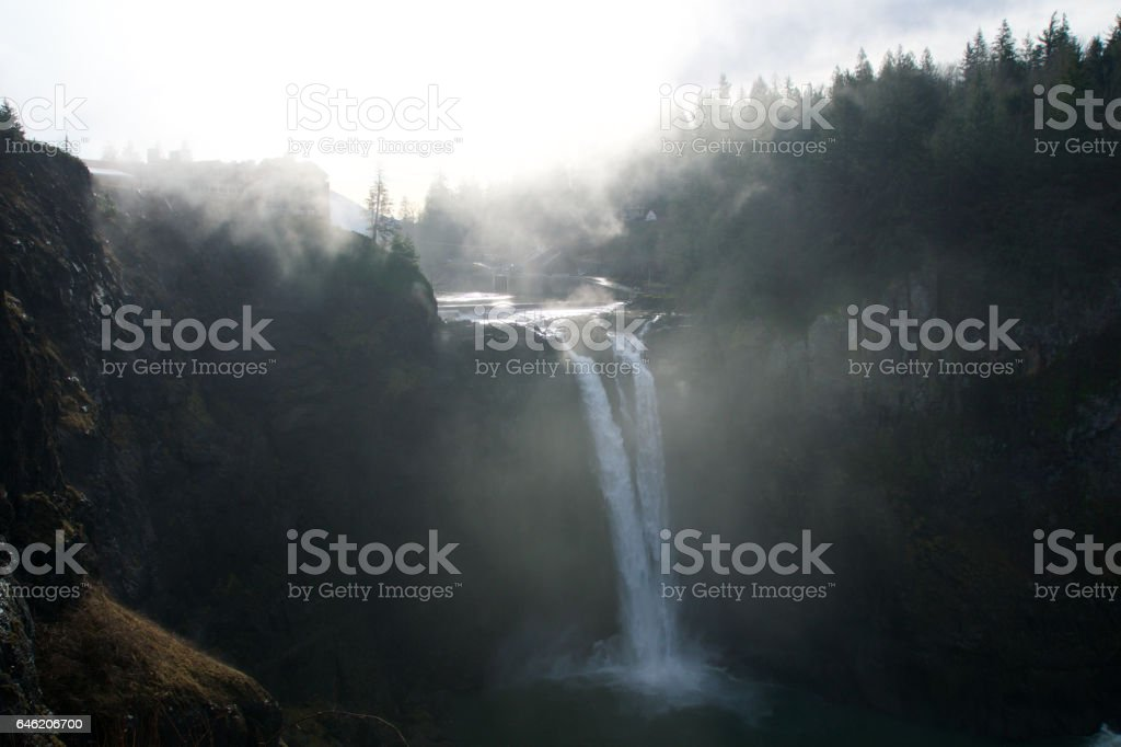 SEATTLE, WASHINGTON STATE, UNITED STATES - Jan 23rd, 2017: tree with the mist, scenic view of Snoqualmie fall when a lot of fog with sun light stock photo