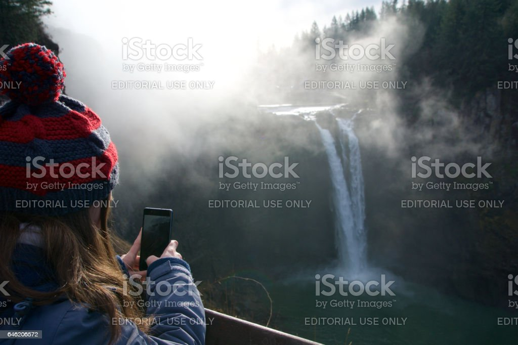 SEATTLE, WASHINGTON STATE, UNITED STATES - Jan 23rd, 2017: tree with the mist, scenic view of Snoqualmie fall with woman taking a photo with her smartphone closeup when a lot of fog with sun light stock photo