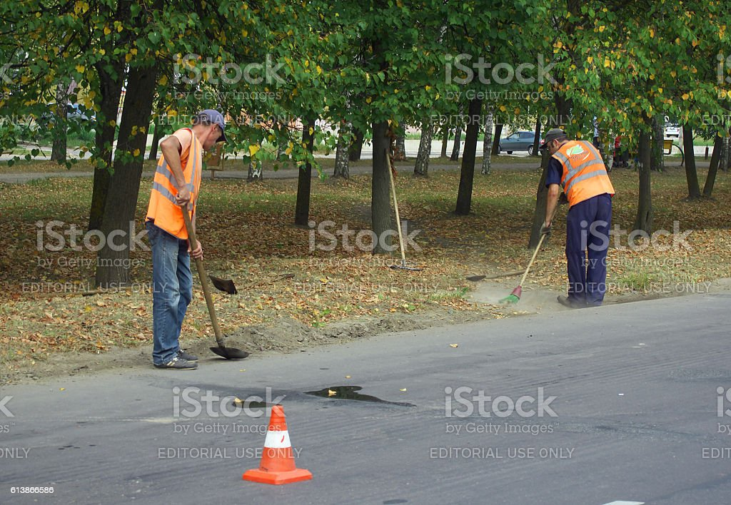 Janitors clean the garbage on the roadside stock photo