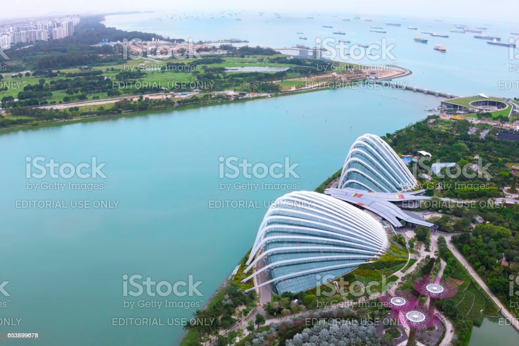 SINGAPORE - January 29 2017 : Cloud Forest & Flower Dome at Gardens by the Bay and Cargo ships entering one of the busiest ports in the world, view from the roof top at Marina Bay Sands. stock photo