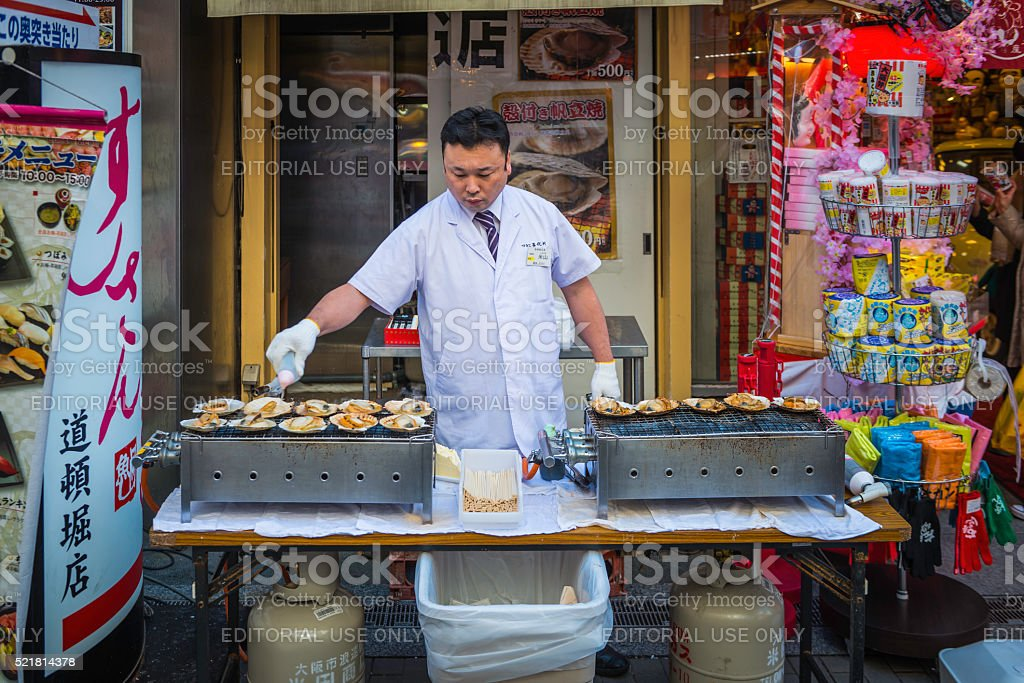 Japan chef grilling traditional seafood snacks street market stall Osaka stock photo