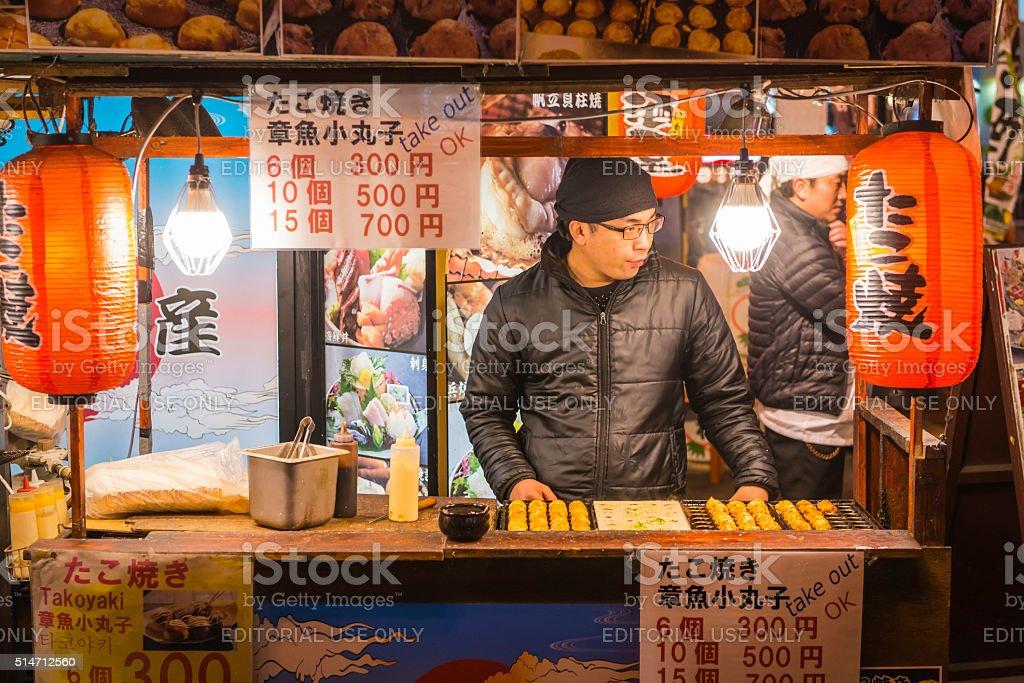 Japan cook selling takoyaki snack food night market stall Osaka stock photo