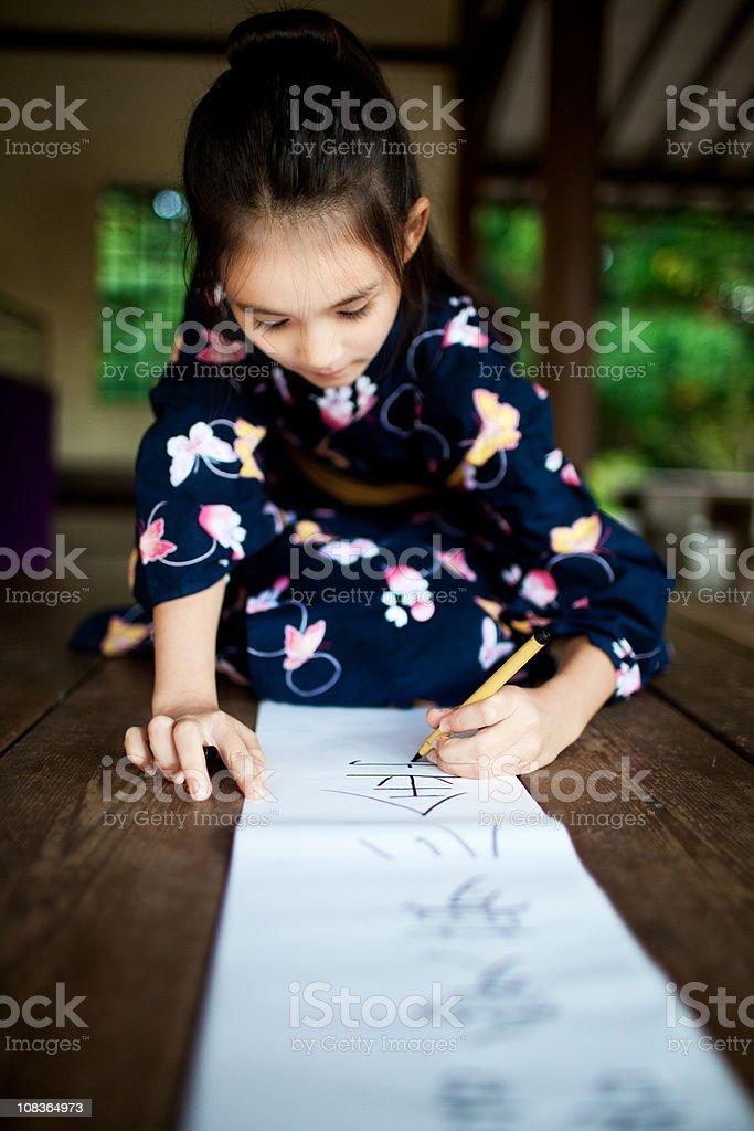 Japan girl writing kanji royalty-free stock photo