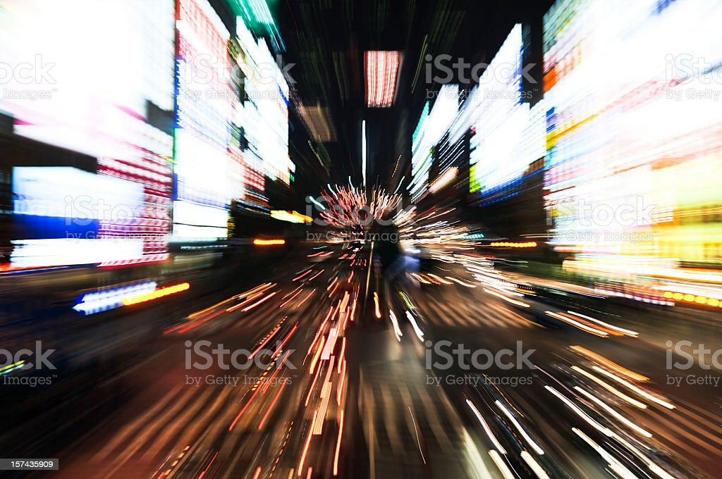 A zoomed blur of cars and bright advertising in Shinjuku, Tokyo.