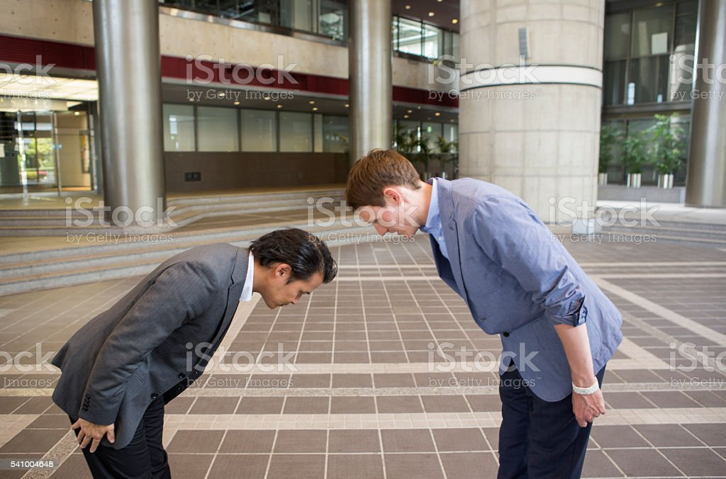 japanese and european businessmen salute at kyoto japan stock photo