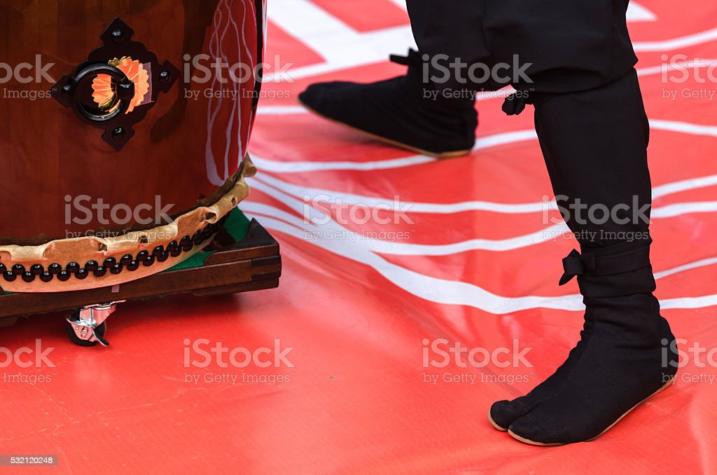 Japanese artist playing on traditional taiko drums stock photo