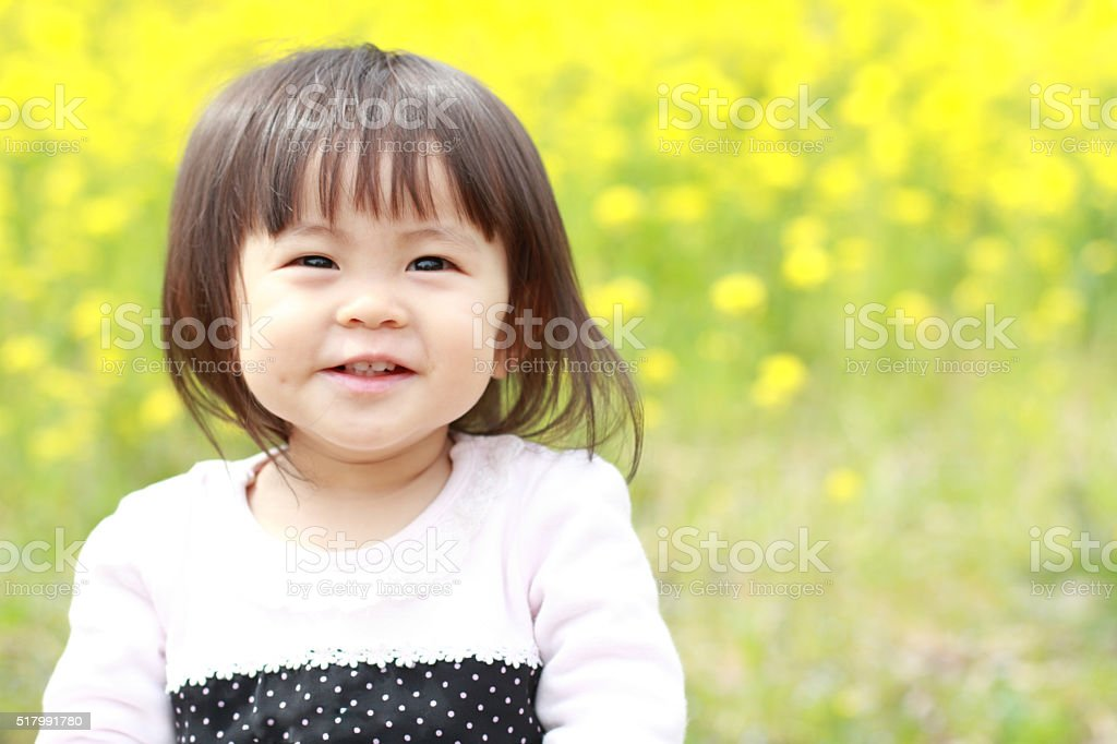 Japanese baby girl (1 year old) and yellow field mustard stock photo