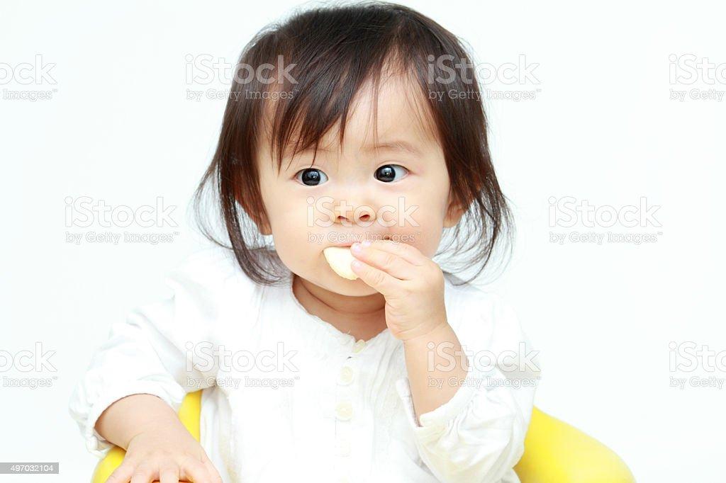 Japanese baby girl eating rice cracker stock photo