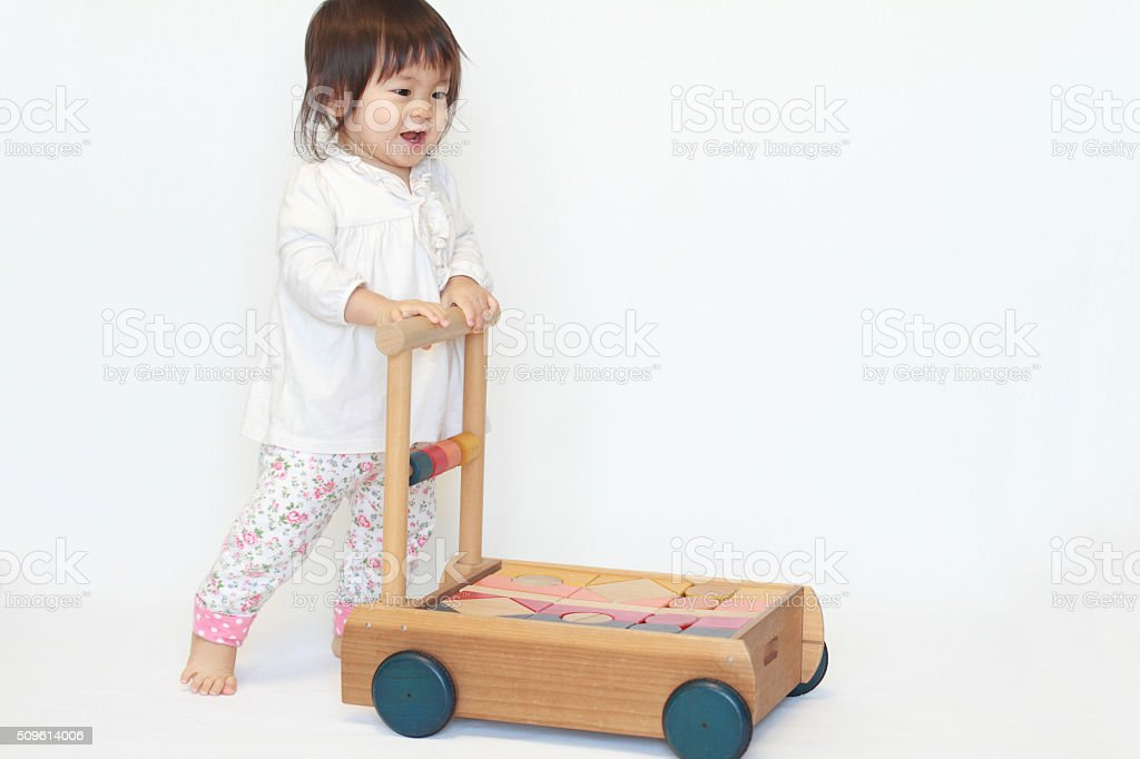 Japanese baby girl pushing a cart (1 year old) stock photo