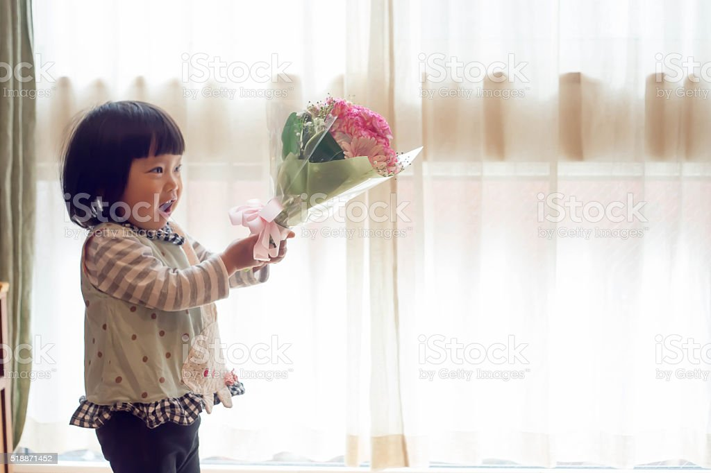 Japanese Baby Girl With Carnation Flower. stock photo