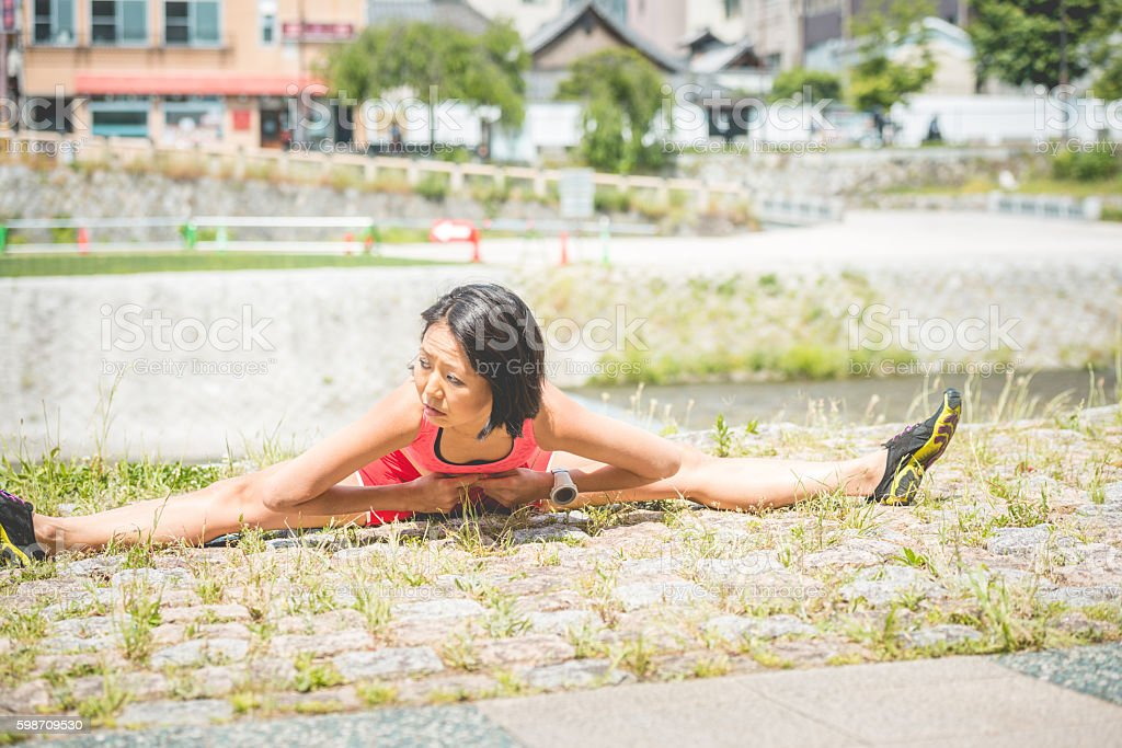 Japanese Bicycle Rider Doing Yoga by Kamo River, Kyoto, Japan stock photo
