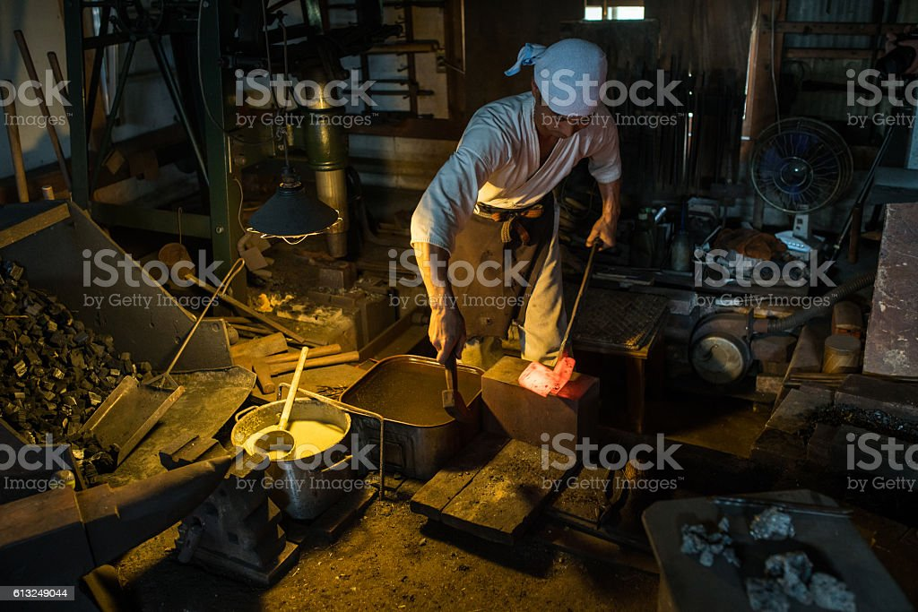 Japanese blacksmith hammers hot steel in his forge stock photo