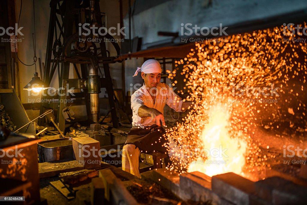 Japanese blacksmith stokes a fire preparing to forge a sword stock photo