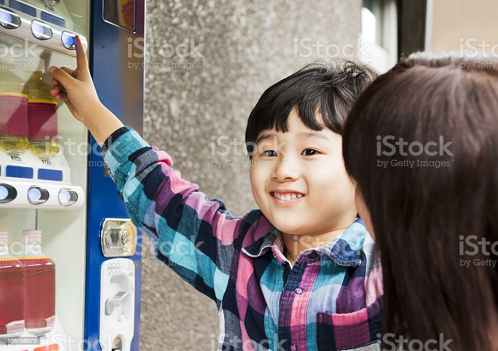 Japanese boy, buying drink from a vending machine. stock photo