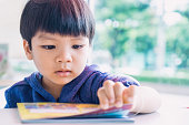 Japanese boy is reading a educational play book.