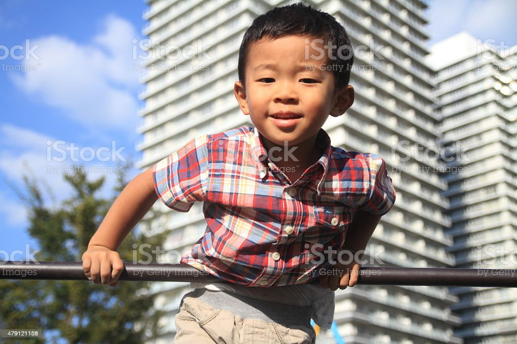 Japanese boy playing with high bar stock photo