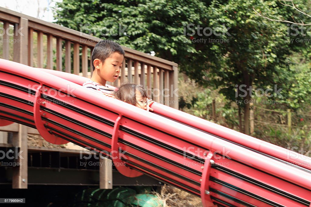 Japanese brother and sister on the slide stock photo